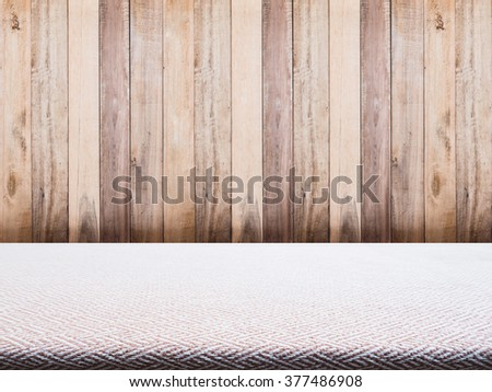 Beige tweed fabric tablecloth and wooden background for product display - stock photo