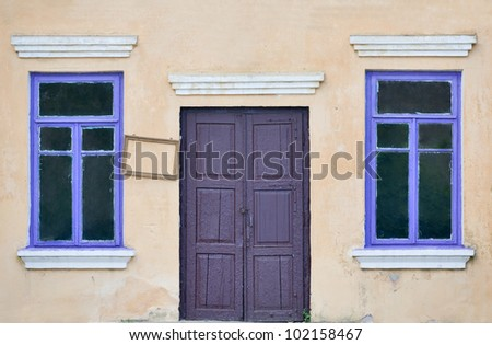 beige wall with door and two windows