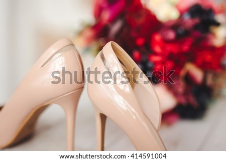 beige wedding shoes with bouquet of flowers - stock photo