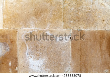 Beige, yellow, brown floor tiles. Aged sand stone brick wall background - stock photo
