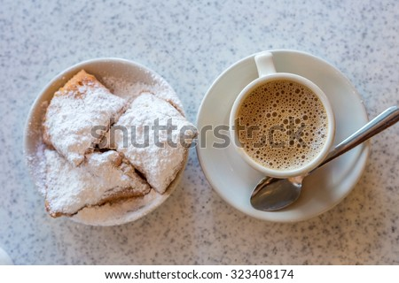 Beignets (French style donuts) topped with sugar and a cup of coffee in the background - stock photo