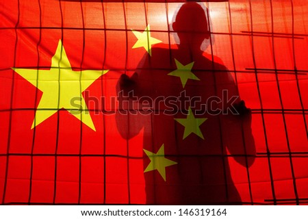 BEIJING - APR 24:Silhouette of Chinese behind fence and China flag on April 24 2009.There are about 1.5 million people in prison in China. China does not allow outsiders to inspect the penal system - stock photo