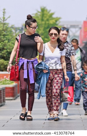 BEIJING-APRIL 28, 2016. Fashionable girls Beijing downtown. Chinese youngsters sees fashion as a way to reflect aspirations and identity. Fashion brands effort to conquer the lucrative Chinese market. - stock photo