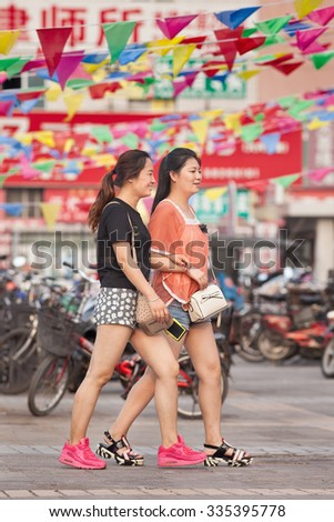 BEIJING-AUGUST 5, 2015. Two young girls dressed in hot pants in a shopping area. Chinese police are warning women not to wear mini-skirts or hot pants to avoid sexual harassment on public transport. - stock photo