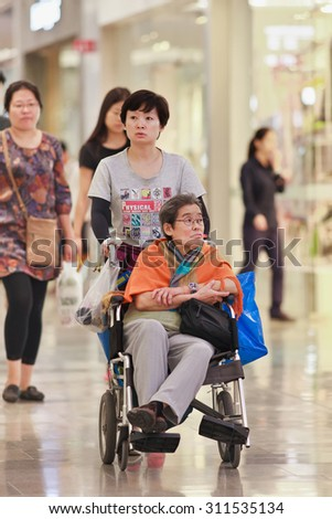 BEIJING-AUGUST 19, 2015. Woman with elder mother at shopping mall. China's elderly population (60 or older) is about 128 million, 10% of its population, China will have 400 million elderly by 2050. - stock photo