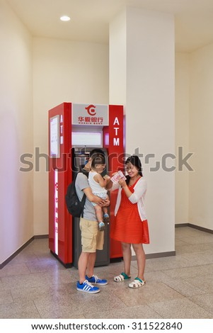 BEIJING-AUGUST 21, 2015. Young couple with child at ATM. According CNN, the average annual salary of a worker in China's private sector was 28,752 yuan ($4,755) in 2012, or 38% of the global average.