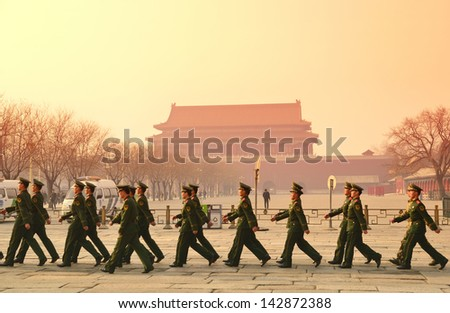 BEIJING, CHINA - APR 1: Team of soldier walk by Tiananmen in the morning on April 1, 2013 in Beijing, China. It is a famous monument in Beijing and serves as a national symbol. - stock photo