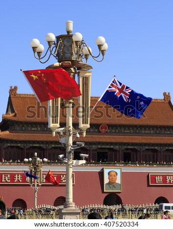 BEIJING, CHINA - APRIL 17, 2016: New Zealand and Chinese National flags flutter on a lamppost at Tiananmen Square during the visit of New Zealand Prime Minister John Key in China. - stock photo