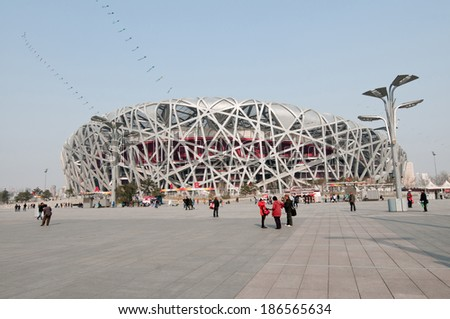 BEIJING, CHINA - APRIL 2: Tourists walks in front of National Stadium in Chaoyang District, commonly known as Bird's Nest on April 2, 2013 in Beijing - stock photo