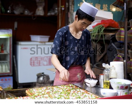 Beijing, China-August 1, 2013: A Uighur man sells melon in Beijing, China on a hot summer day