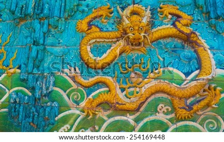 BEIJING, CHINA, AUGUST 21, 2013: detail of the golden dragon on the wall of the forbidden city palace complex in beijing. - stock photo