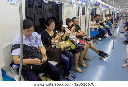 BEIJING, CHINA -AUGUST 28,2015: Passengers use their mobile phones in a subway train. Mobile phones and tablets are used for people to entertain and view information when taking public transportation. - stock photo
