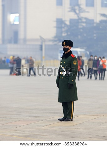 BEIJING, CHINA - DECEMBER 20, 2015: A Chinese military man wears a face mask at Tiananmen Square. Beijing issued a red alert for air pollution on Friday, its second red alert this month.  - stock photo