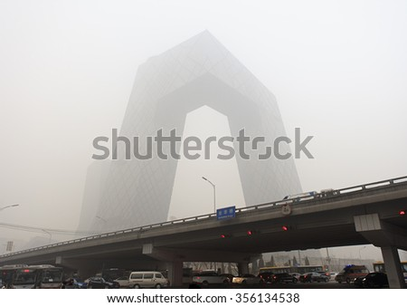 BEIJING, CHINA - DECEMBER 25, 2015: China Central Television (CCTV) Headquarters is shrouded by thick smog. More than 200 flights were canceled as heavy smog shrouded the city on Christmas Day. - stock photo