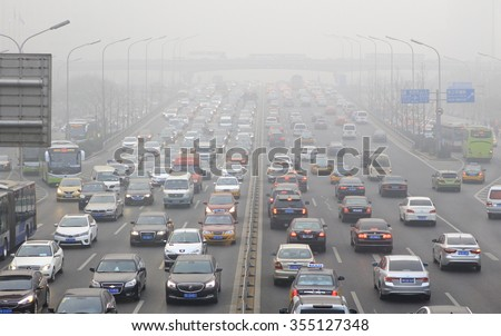 BEIJING, CHINA - DECEMBER 25, 2015: Traffic is seen at Guomao area in heavy smog. Today more than 200 flights were cancelled at the Beijing International Airport as heavy smog shrouded the city.