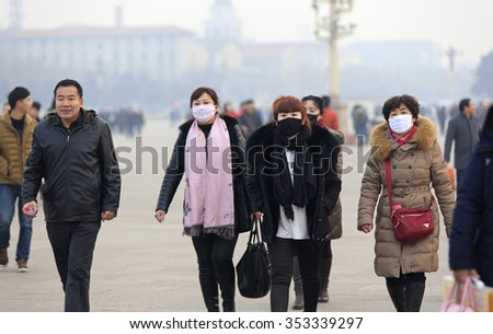 BEIJING, CHINA - DECEMBER 20, 2015: Unidentified people wear face mask at Tiananmen Square. Beijing issued a red alert for air pollution on Friday, its second red alert this month.