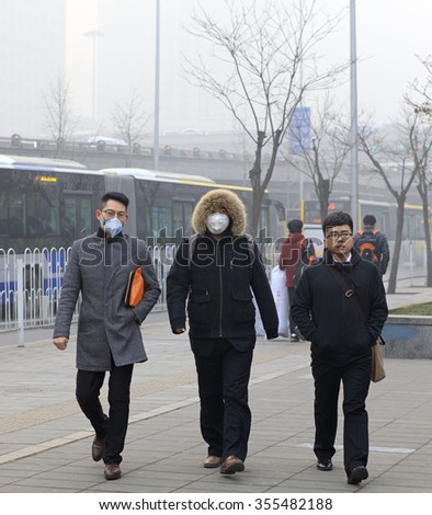 BEIJING, CHINA - DECEMBER 25, 2015: Unidentified people wear face mask in smog, around Guomao area. More than 200 flights were canceled as heavy smog shrouded the city on Christmas day. - stock photo