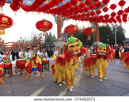 BEIJING, CHINA - FEBRUARY 8, 2016: Folk artists, dressed in traditional costumes, perform lion dance at the entrance of the Ditan Park, on the first day of the Chinese New Year, the year of the monkey