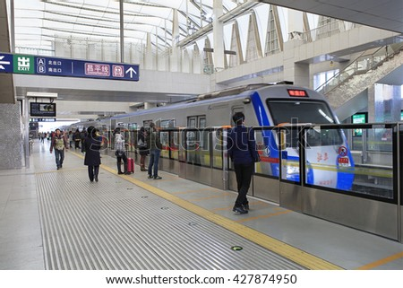 BEIJING, CHINA - FEBRUARY 4, 2016: Passengers are seen at a subway station waiting platform as train arrives. Beijing's 18 subway lines carry over 10 million passengers on an average weekday.  - stock photo