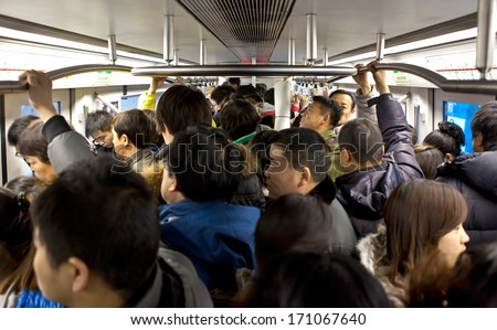BEIJING, CHINA - JAN. 12, 2014: Crowded subway train during rush-hour. Any subway trip, costs only 2 yuan (33 US cents); Beijing government's  plans to reform the current low-cost subway ticket system - stock photo