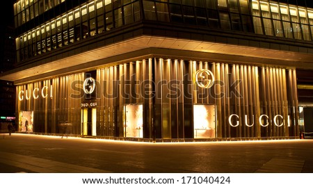 BEIJING, CHINA - JAN. 12, 2014: Gucci store at night. Gucci is an Italian fashion and leather goods brand was founded by Guccio Gucci in Florence in 1921. Gucci has about 425 stores worldwide. - stock photo