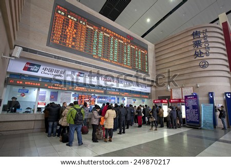 BEIJING,CHINA-JAN. 29, 2015: Passengers buy their tickets  at the Beijing South Railway station. Around 2.807 billion trips are expected to be made by people during China's Spring Festival travel rush
