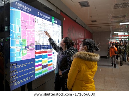BEIJING,CHINA - JAN.11, 2014: Passengers take a look of the subway map. Any subway trip, costs only 2 yuan (33 US cents); Beijing government's plans to reform the current low-cost subway ticket system - stock photo