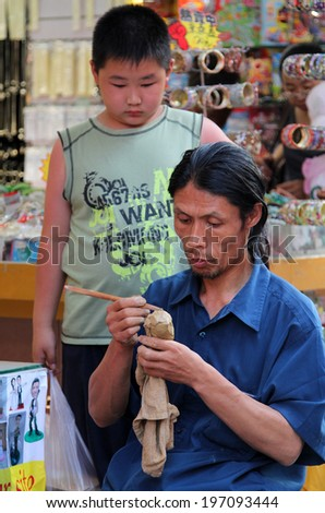 BEIJING, CHINA - JUL 3, 2011: craftsman making souvenirs on the street, not far from Tiananmen square