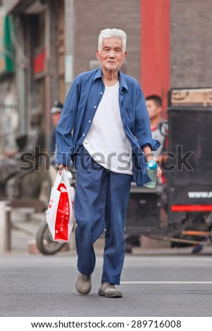 BEIJING, CHINA -JUNE 9, 2015. Handsome old man in city center. Elderly population (60 or older) in China is 128 million, one in every ten people, the world's largest. China has 400 million elderly by 2050. - stock photo