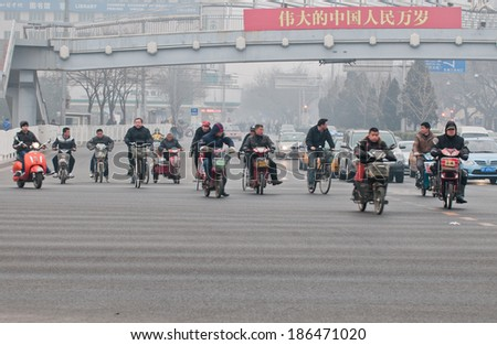 BEIJING, CHINA - MARCH 31: Chinese people rides on motor scooters on a busy street in Dongcheng District on March 31, 2013 in Beijing - stock photo