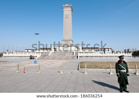 BEIJING, CHINA - MARCH 27: Chinese soldiers stands on attention in front of Monument to the People's Heroes on Tiananmen Square on March 27, 2013 in Beijing - stock photo