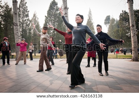 Beijing, China - March 26, 2013: Chinese women during mornig dance exercises in Temple of Heaven park area - stock photo