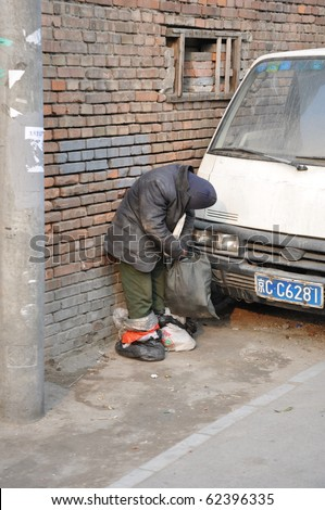 BEIJING, CHINA - MARCH 06: Unidentified poor Chinese man standing while sleeping March 6, 2010 in Beijing, China. The poor and homeless people have a hard time during the winter in the Hutong areas