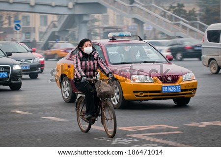 BEIJING, CHINA - MARCH 31: Woman with protective mask rides bike on a busy street in Dongcheng District on March 31, 2013 in Beijing - stock photo
