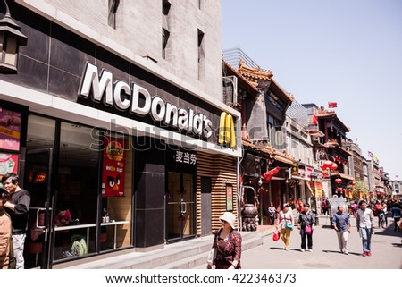 BEIJING, CHINA - May 3, 2016: people walks next to McDonald's restaurant at one of the renovated perpendicular street to famous Qianmen Dajie pedestrian commercial street.