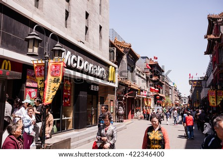 BEIJING, CHINA - May 3, 2016: people walks next to McDonald's restaurant at one of the renovated perpendicular street to famous Qianmen Dajie pedestrian commercial street. - stock photo