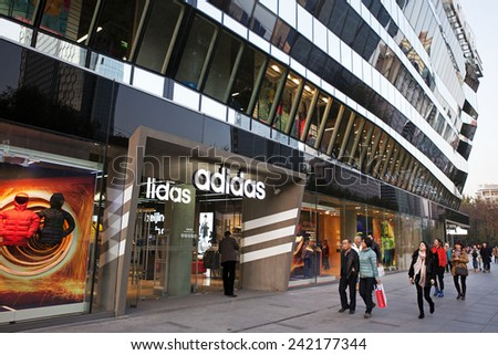 BEIJING, CHINA - NOV. 22, 2014: Shoppers are seen at a Adidas store; Adidas, a German multinational corporation founded in 1948, is the second biggest sportswear manufacturer in the world. - stock photo