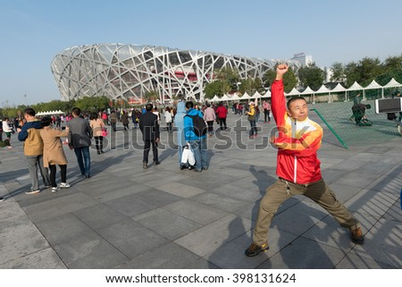 Beijing, China - October 25, 2015: Local tourist wearing the official top of the Olympic China team posing for a photograph at the front of the Beijing National Stadium also known as the Bird's Nest.