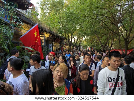 BEIJING, CHINA - OCTOBER 3, 2015: People crowd Nanluoguxiang, an ancient part of the city, during the National Day holiday, the 66th anniversary of the founding of the People's Republic of China. - stock photo