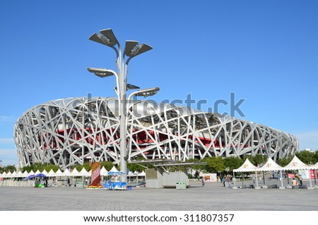 Beijing, China, October, 10, 2012. People walking near Bird's Nest in autumn day. The Bird's Nest is a stadium in Beijing, especially designed for use throughout the 2008 Summer Olympics Games