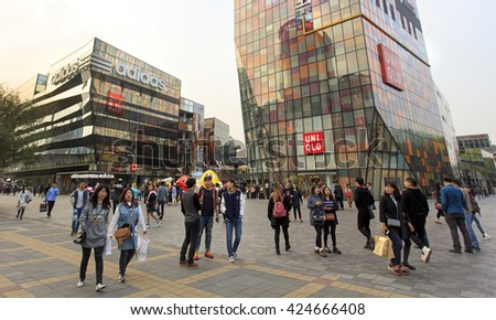 BEIJING, CHINA - OCTOBER 18, 2015: Unidentified people are seen around Taikoo Li Sanlitun. Taikoo Li Sanlitun is a shopping centre comprises of 19 buildings and is located in the Sanlitun area - stock photo