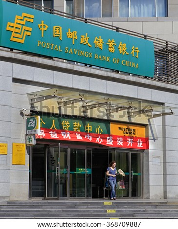 BEIJING, CHINA - SEPTEMBER 12, 2015: An unidentified woman is seen at the entrance of a Postal Savings Bank of China. This is a commercial retail bank that has around 40,000 branches in China.