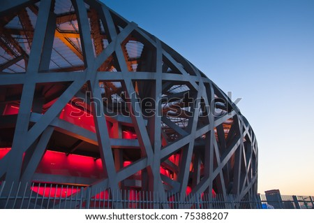 """BEIJING-CIRCA APRIL 2011:Dusk falls at the National Stadium in Beijing circa April 2011. Also known as the """"Bird's Nest"""", it draws 20,000 to 30,000 visitors a day, despite lack of significant events. - stock photo"""