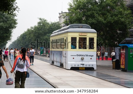 BEIJING - CIRCA JUNE, 2015: Tram in the Qianmen shopping Pedestrian Street is located in the old center of Beijing. Buildings on the street underwent restoration, where many world-famous trade brands - stock photo