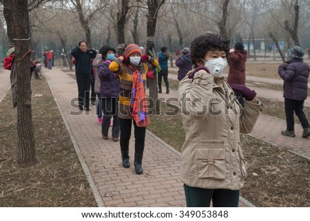 BEIJING - DEC 8: mask-covered Beijing residents doing outdoor exercise on December 8, 2015 in Beijing, China.The Chinese government issued the historical first Red Alert on air pollution on this day. - stock photo