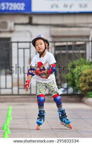 BEIJING-JULY 10, 2015. Boy practicing inline skating. Although Ping-Pong, basketball and badminton are China's top sports, last decade inline skating became increasingly popular among Chinese youth.  - stock photo