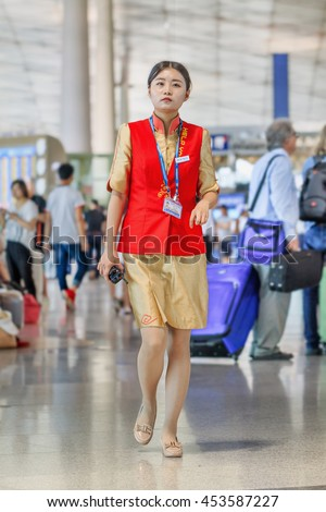BEIJING-JULY 13, 2016. Charming hostess with a Porto phone at Beijing Capital International Airport, Terminal 3, with 986,000 square meter the second largest airport terminal building in the world.