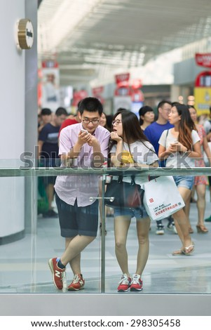 BEIJING-JULY 18, 2015. Couple busy with smart phone in a shopping mall. China has currently 519.7 million smartphone users. That figure will rise to 574.2 million Chinese smartphone users by 2015. - stock photo