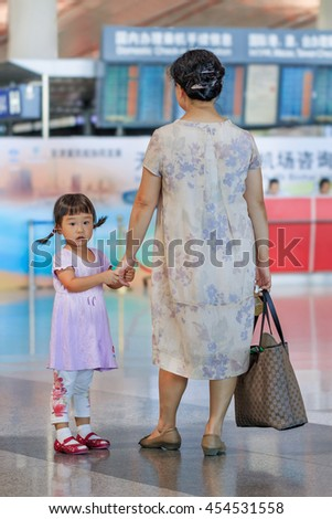 BEIJING-JULY 13, 2016. Cute girl with her grandmother waiting at Beijing Capital International Airport, Terminal 3, with 986,000 m2 it is the second largest airport terminal building in the world. - stock photo