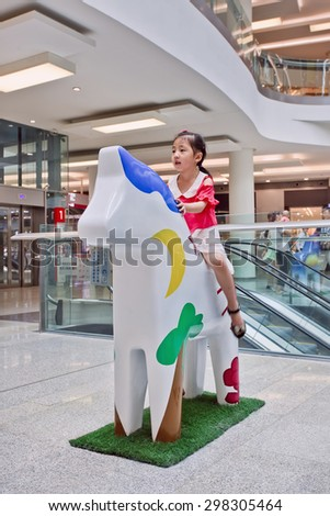 BEIJING-JULY 18, 2015. Girl on DALA horse, Livat shopping mall. The mall is owned by Swedish Ikea Group and shoppers will experience Scandinavian design like DALA horse, national symbol of Sweden.  - stock photo